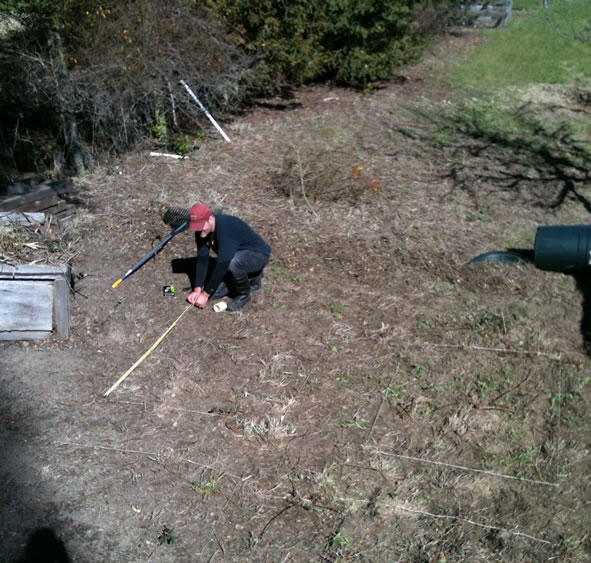 using a tape measure to plot spaces for raised garden beds